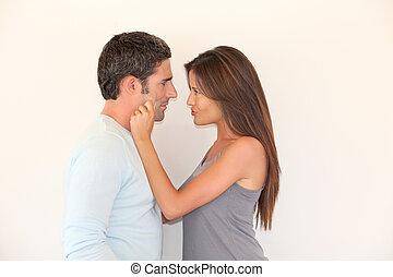 Woman pulling on boyfriend's cheeks