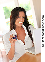 Woman drinking coffee in front of laptop computer at home
