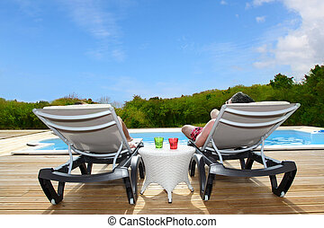 Back view of people relaxing on pool deck chairs