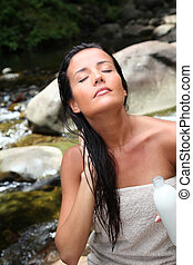 Beautiful young woman applying hair conditioner sitting by...