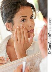 Retrato, bonito, mulher, aplicando, anti-wrinkles, creme