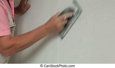 Man Sanding Plaster - Man's hand sanding plaster on a new...