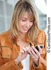Woman in town sending short message with mobile phone