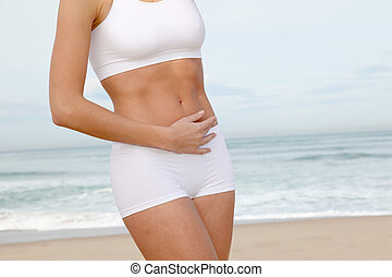 Closeup of womans body stretching on the beach