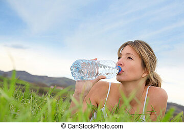 Beautiful blond woman drinking water in natural landscape