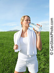 Woman drinking water from water during fitness activity