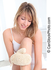 Beautiful woman using rubbing glove