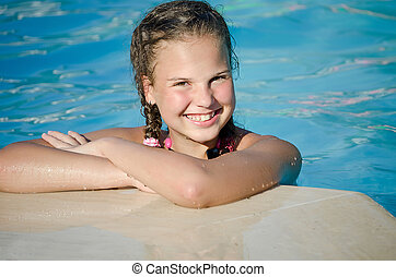 The young girl in pool - The beautiful smiling young girl in...