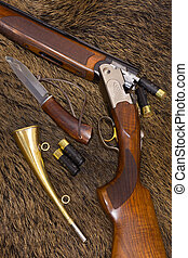 shotgun, cartridges, knife and hunt on top of a boar skin