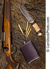 rifle, cartridges, knife and flask on top of a boar skin