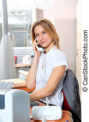 Blond woman talking on the phone in front of desk computer