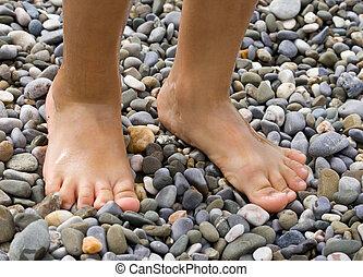 Childish legs on pebble