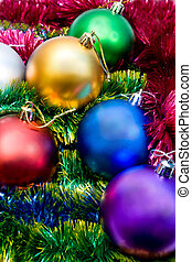 Multi-colored Christmas tree balls in the tinsel