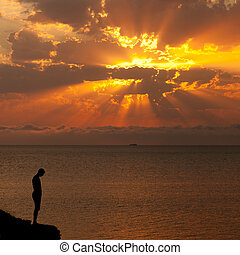 Silhouette of a man on a cliff above the sea at sunset