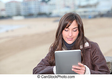 Young woman using electronic pad by the beach in winter