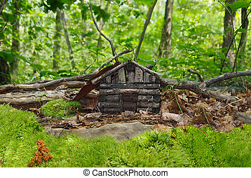 Faerie House - A tiny log cabin faerie dwelling sits hidden...