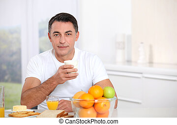 Smiling adult man having breakfast