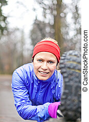 Woman runner stretching and exercising in winter forest