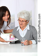 Nurse bringing medicine to elderly woman