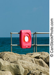 Lifebelt case mounte d on railings ona breakwater with sea...