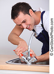 Young man fixing sink
