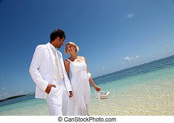 Just married couple walking on a sandy beach