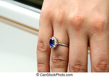 Round sapphire and diamond ring on finger of hand
