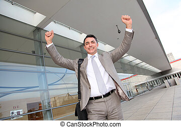 Smiling businessman with arms up