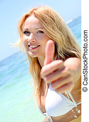 Beautiful blond woman in the sea showing thumbs up