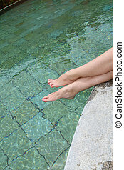 Closeup on woman's legs by swimming pool