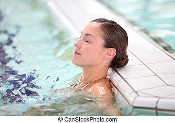 Beautiful young woman relaxing in seawater pool