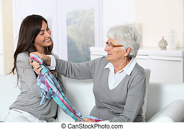 Young woman showing new clothes to grandmother