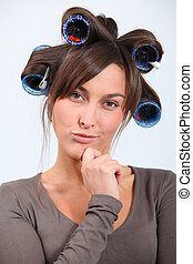 Beautiful woman with hair-curlers doing funny faces