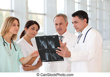 Group of doctors and nurses looking at xray