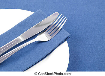 Cutlery on blue napkin on white plate