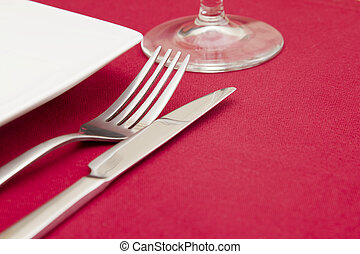 Elegant place setting on red tablecloth