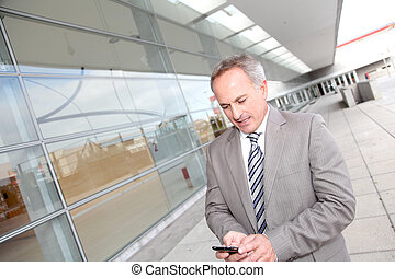 Businessman with mobile phone in front of modern building