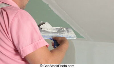House Renovation - Plastering - Man applying plaster on a...