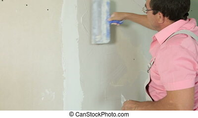 Plastering a New Wall - Man applying plaster on a new...