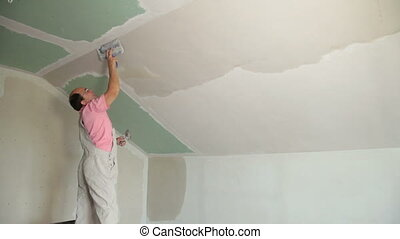 Man Plastering Wall of Attic - Man applying plaster on a new...
