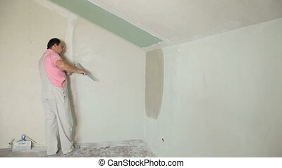 Man Plastering Wall - Man applying plaster on a new drywall...