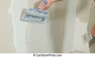 Plastering a Wall - Man's hand applying plaster on a new...