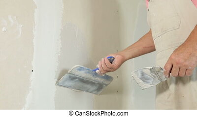 Applying a Coat of Plaster - Mans hand applying plaster on a...