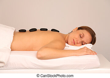Woman having a massage with hot stones