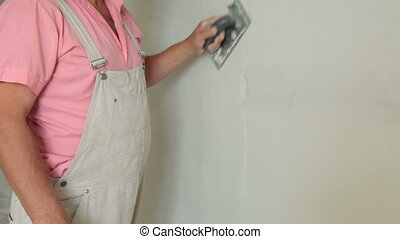 Plasterer Sanding Drywall - Man sanding plaster on a new...