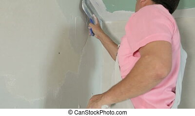 Plastering a Drywall - Man applying plaster on a new drywall...