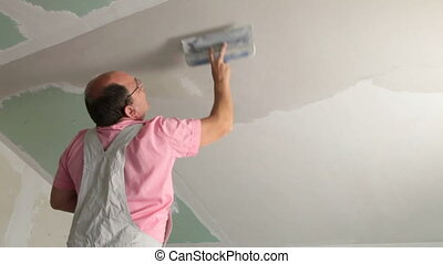 Plastering Ceiling - Man applying plaster on a new drywall...