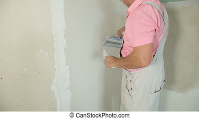 Applying Plaster - Man applying plaster on a new drywall...