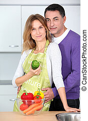 Couple in kitchen with bowl of vegetables