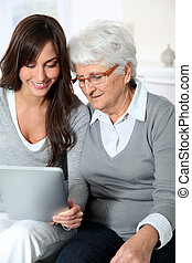 Elderly woman with granddaughter with laptop computer